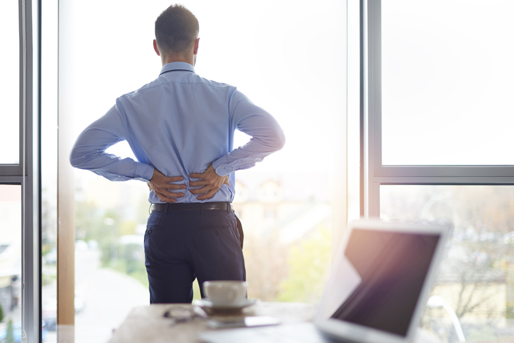 Man with back pain at work.